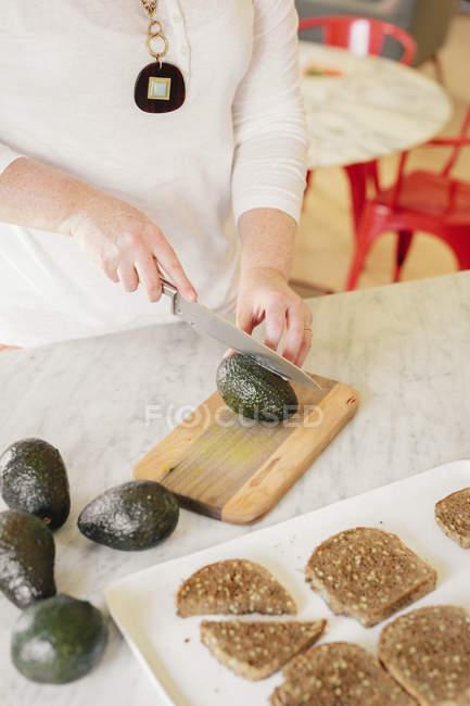 Woman slicing an avocado — Stock Photo