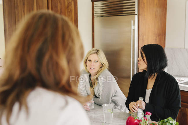 Women talking together in a kitchen — Stock Photo