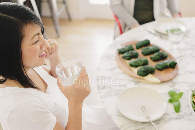 Femme assise à une table — Photo de stock