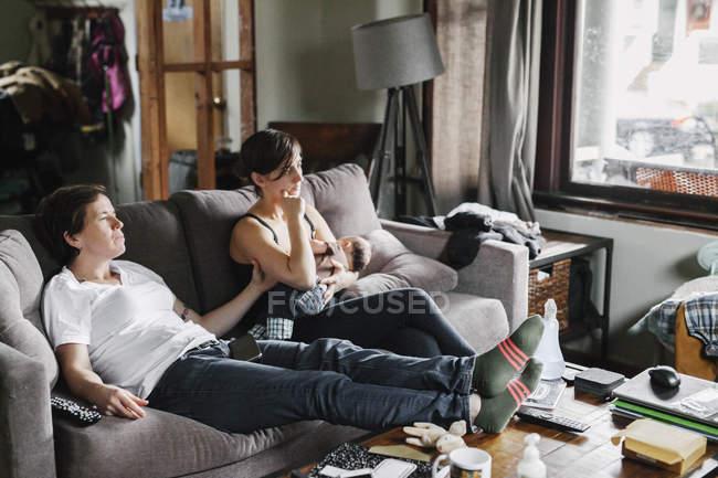 Пару на дому, сидячи на дивані — стокове фото