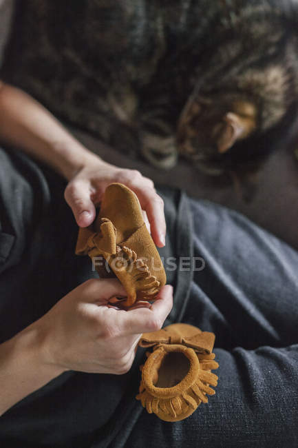 Woman seated holding two baby bootees. — Stock Photo