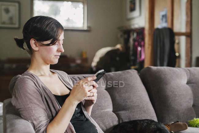 Woman on the sofa using her smart phone — Stock Photo