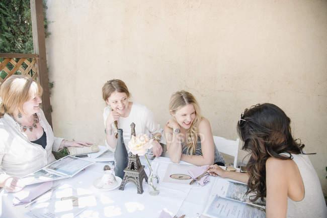 Чотирма усміхнені жінок сидить за столом — стокове фото