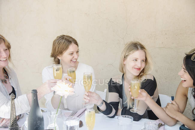 Four smiling women sitting at a table — Stock Photo