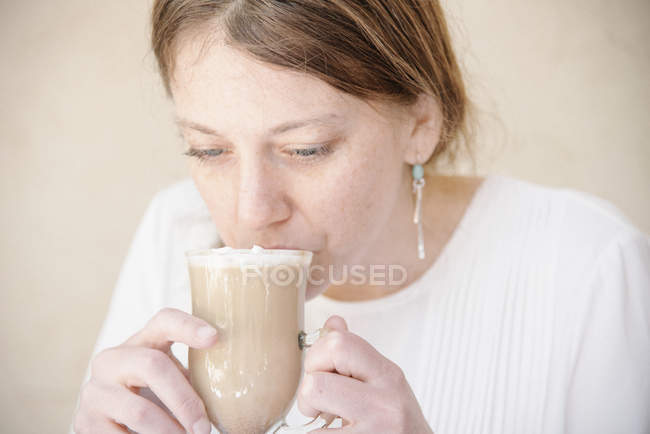 Portrait of woman drinking a cafe latte. — Stock Photo