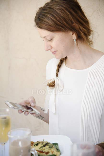 Портрет женщины, глядя на ее сотовый телефон — стоковое фото