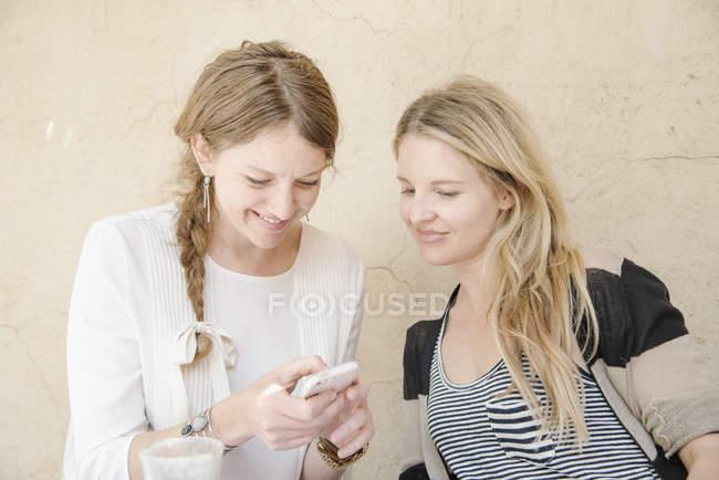 Mulheres a olhar para um telefone celular — Fotografia de Stock