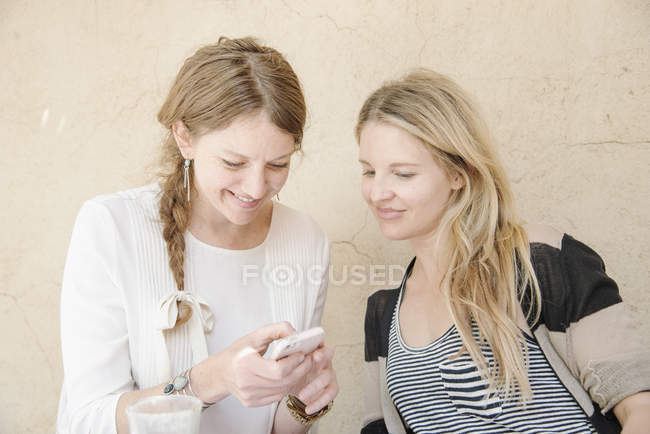 Women looking at a cell phone. — Stock Photo