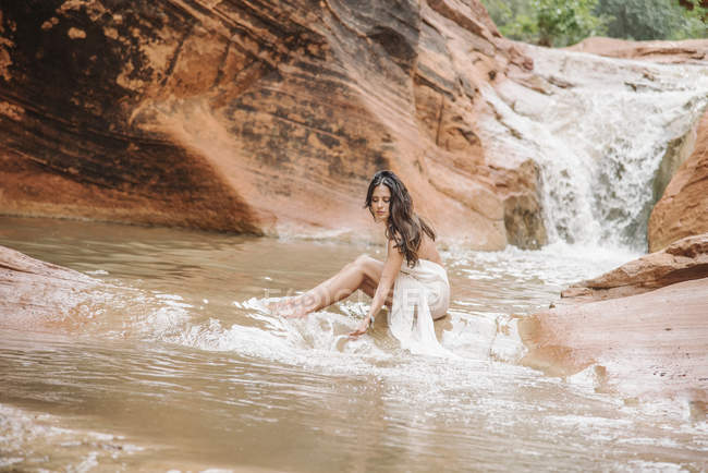Woman sitting on a rock in a river. — Stock Photo