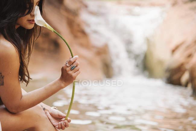 Frau riechen eine Arum Lilie — Stockfoto