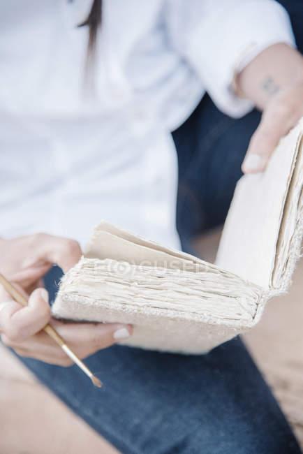 Femme tenant un carnet de croquis — Photo de stock