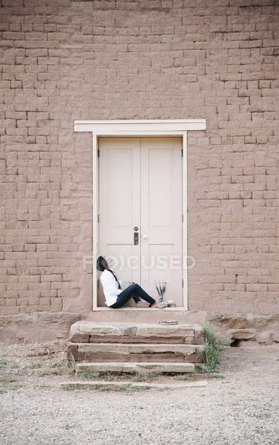Woman sitting on the ground outside the front door of a building. — Stock Photo