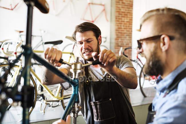 Homens olhando para uma bicicleta — Fotografia de Stock