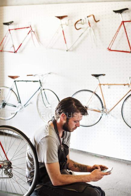 Человек, работающий в магазин ремонт велосипедов — стоковое фото