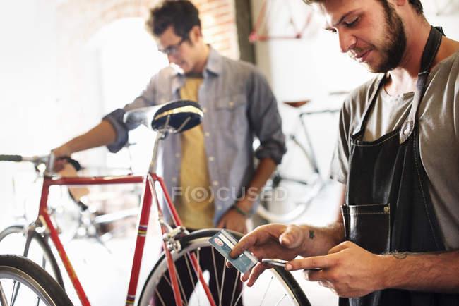 Hombre sosteniendo un teléfono inteligente y tarjeta de crédito . - foto de stock