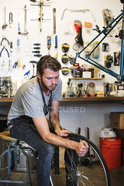 Людина ремонтом у магазин велосипедів. — стокове фото