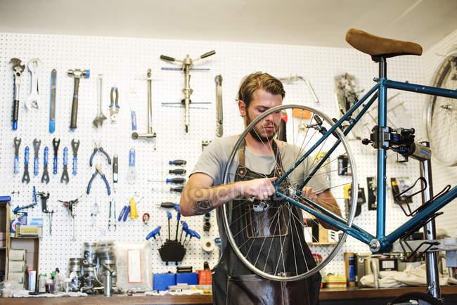 Людина ремонтом у магазин велосипедів — стокове фото
