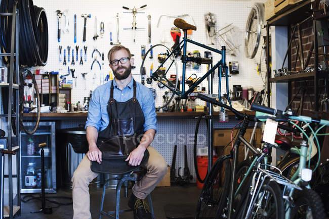 Людина, що працюють в магазин велосипедів. — стокове фото