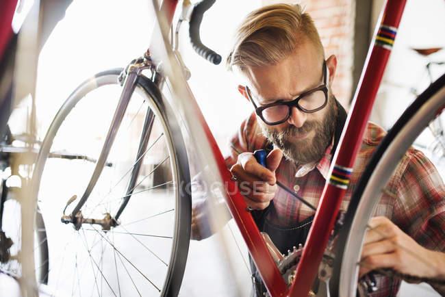 Людина ремонту велосипедів в магазин — стокове фото