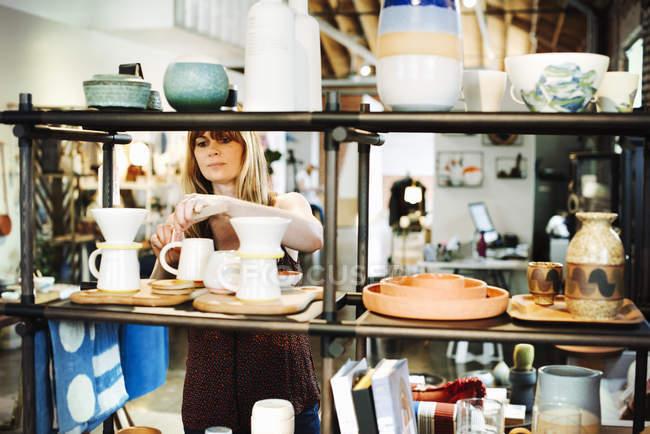 Organiser les objets en céramique sur une étagère de femme — Photo de stock