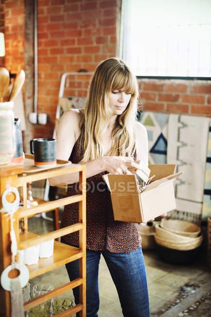 Woman holding a small cardboard box — Stock Photo
