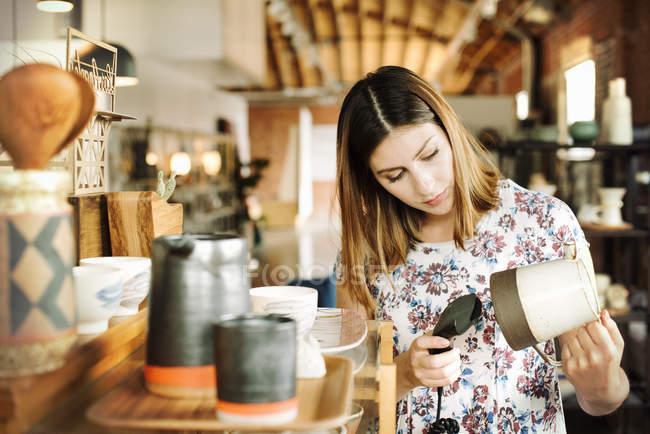 Жінка сканування штрих-коду керамічний глечик — стокове фото