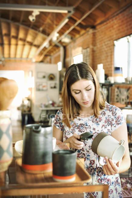 Donna di scansione del codice a barre di una brocca di ceramica — Foto stock