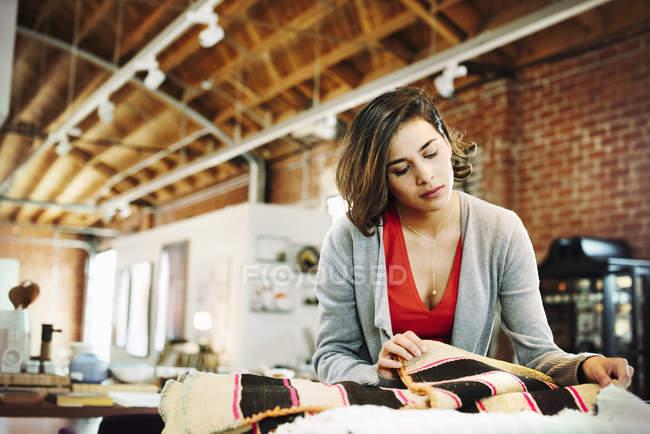 Молода жінка, дивлячись на невеликі килимки смугастий. — стокове фото
