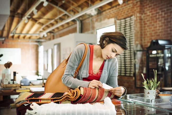 Молода жінка, дивлячись на ціну — стокове фото