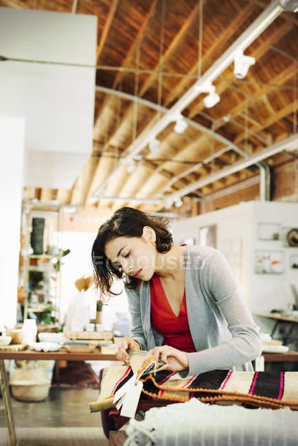 Жінка дивиться на невеликі килимки смугастий. — стокове фото