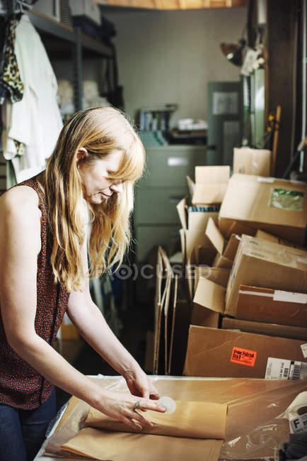 Женщина заворачивает товар в коричневую бумагу . — стоковое фото