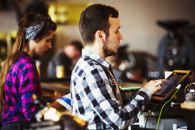Woman and man working behind the counter — Stock Photo
