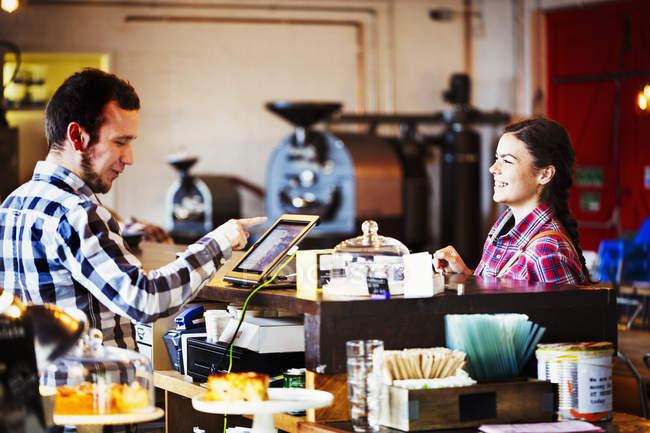 Uomo che utilizza un touch screen per registrare le transazioni — Foto stock
