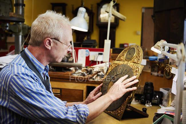 Clockmaker working in his studio — Stock Photo