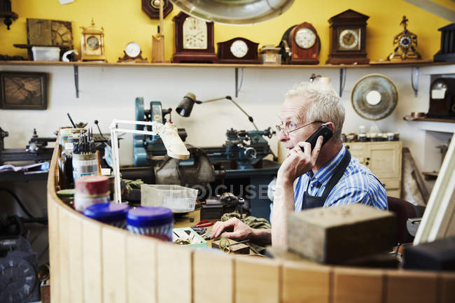 Clockmaker talking on the phone — Stock Photo