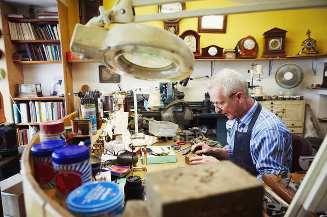 Clockmaker working in his studio — Stock Photo
