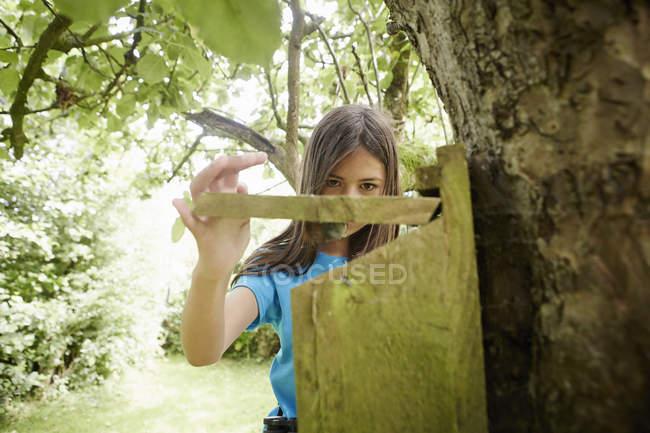 Дівчина перевірка вкладеності коробку на стовбурі дерева. — стокове фото