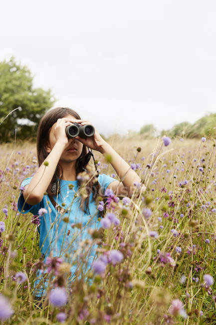 Girl holding binoculars — Stock Photo