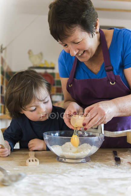 Woman and a child cooking at a kitchen — Stock Photo