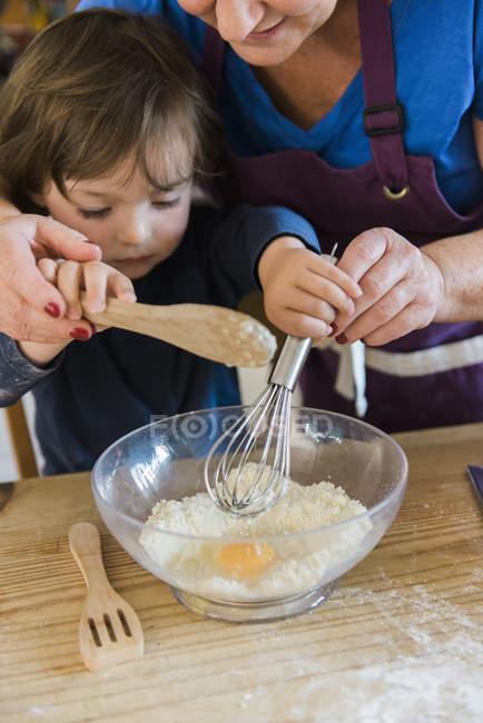 Donna e un bambino che cucinano in cucina — Foto stock