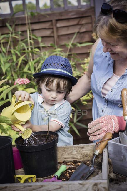 Mulher com criança plantas pote de rega — Fotografia de Stock