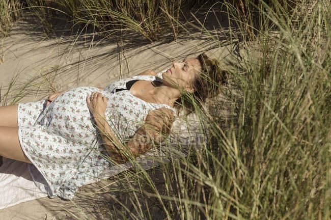 Беременная женщина лежит на солнце — стоковое фото
