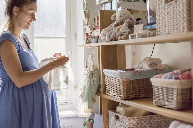 Pregnant woman sorting out baby clothes — Stock Photo