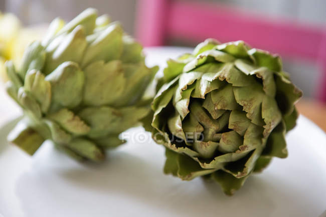 Two artichokes lying on a table. — Stock Photo