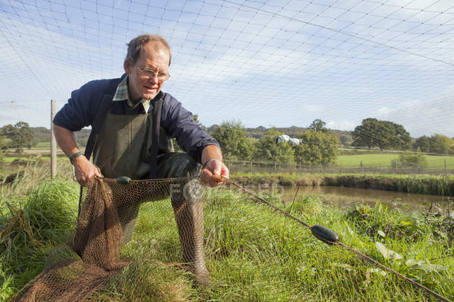 Man handling a large net — Stock Photo