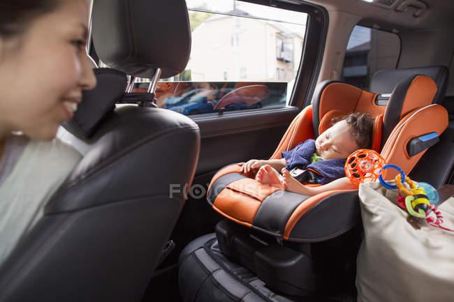 Mãe olhando em seu bebê dormindo — Fotografia de Stock