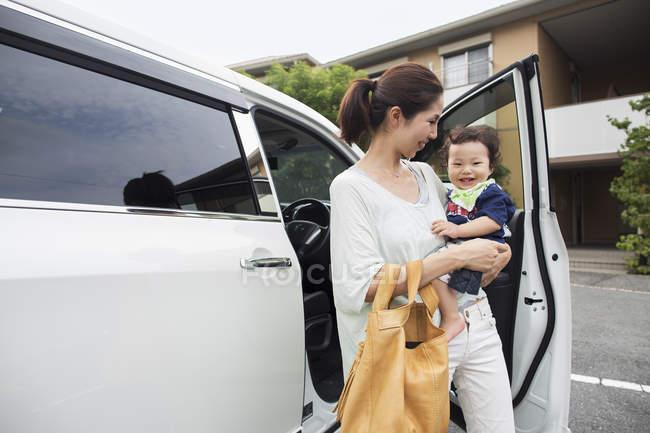 Азіатські мати, несучи її хлопчика — стокове фото