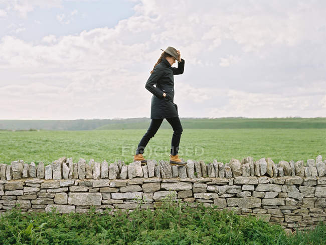 Женщина в шляпе, идущая по вершине — стоковое фото