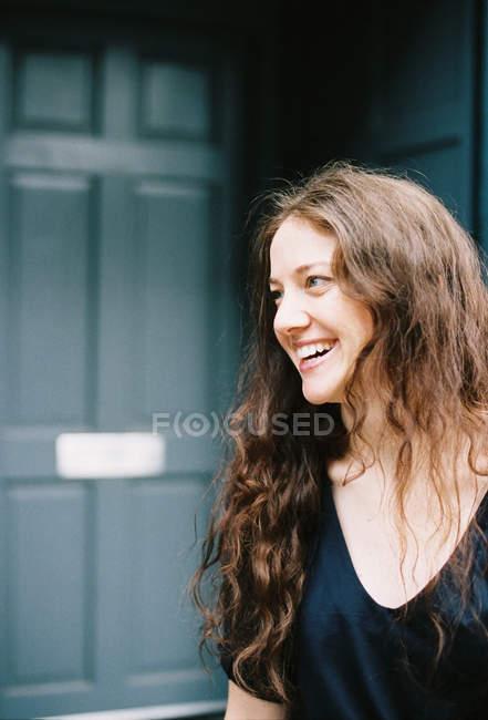 Donna sorridente in piedi ad una porta aperta . — Foto stock