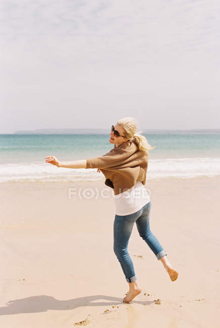 Woman dancing barefoot on the sand — Stock Photo
